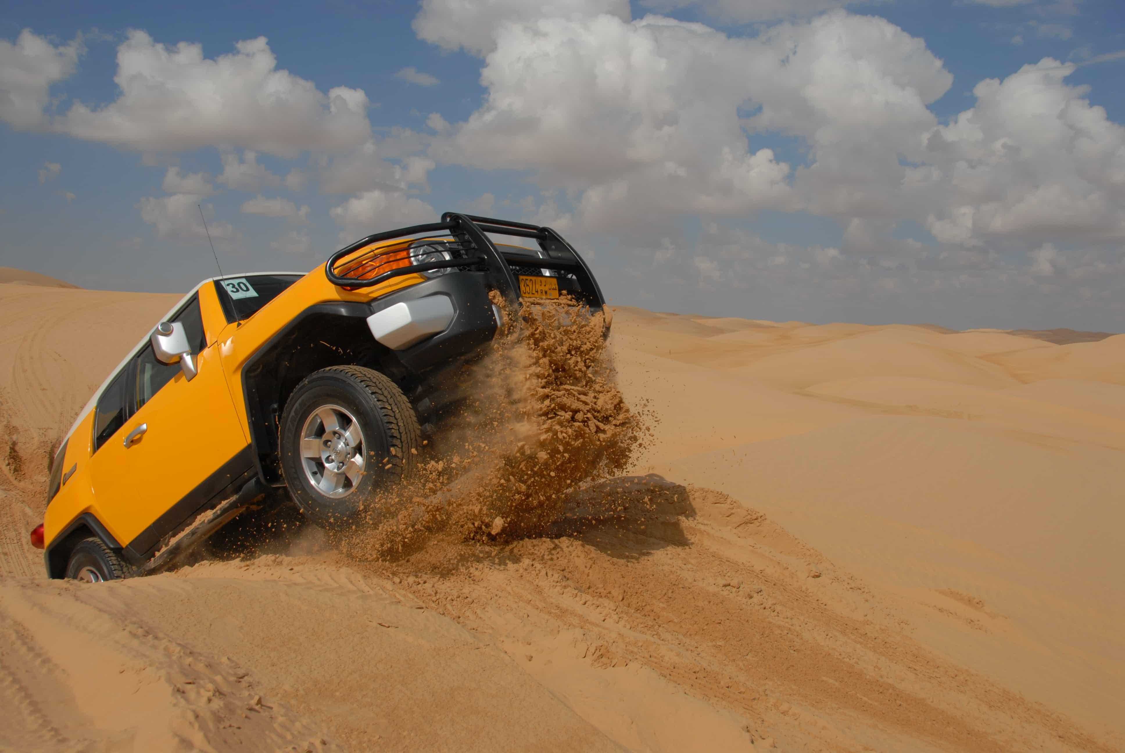 Car driving up dune