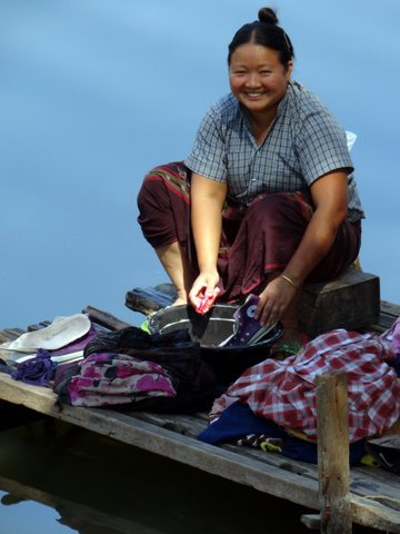 Lady washing by river in Myanmar