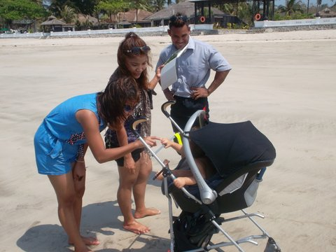 locals in Myanmar on beach with stroller