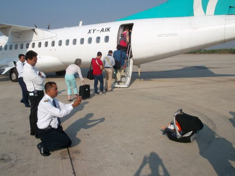 pilot taking photo of baby in Maxi Cosi in front of airplane