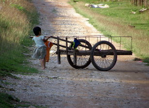 Girl pushing pushcart on gravel road, Travel alone as a woman