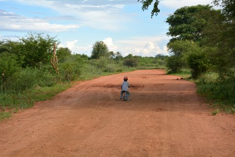 child riding bike on red dirt road, travel with kids, Puky Laufrad