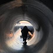 Tipps Reisen mit Kleinkind, kleines Kind läuft aus Tunnelrutsche unten angekommen