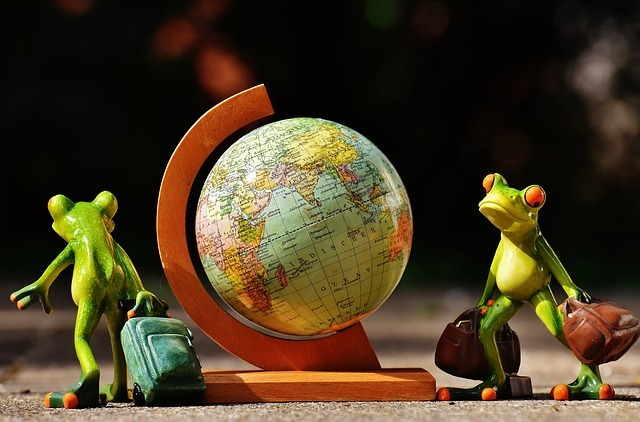 Globe and 2 frogs holding suitcases