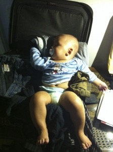 Tipps Reisen mit Kleinkind, schlafendes Baby in Koffer