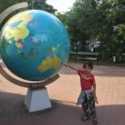 Digitales Nomadentum mit Kleinkind, Kind vor Riesenglobus